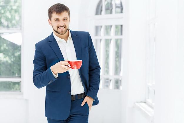 Geschäftsmann, der kaffeepause hat, hält eine tasse