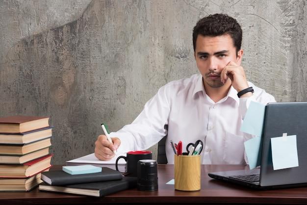 Geschäftsmann, der kamera beim schreiben am schreibtisch betrachtet.