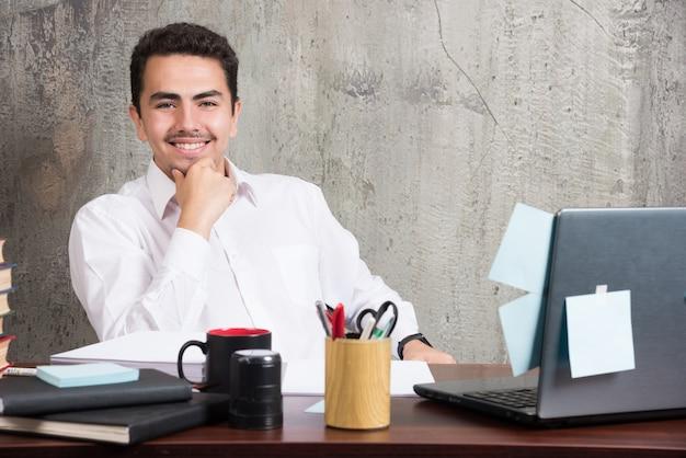 Geschäftsmann, der kamera mit glücklichem ausdruck am schreibtisch betrachtet.