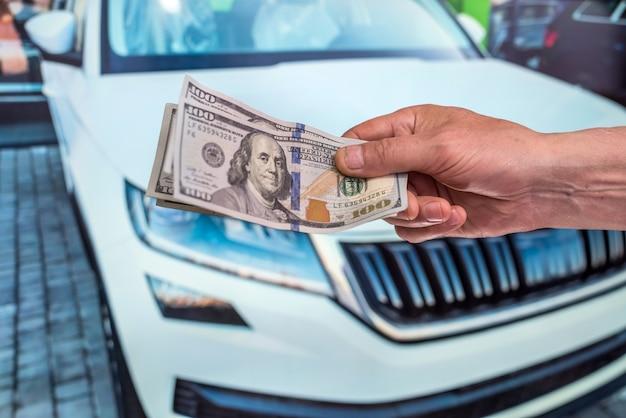 Geschäftsmann, der kauf- oder mietautos tut, die dollarverkäufer geben