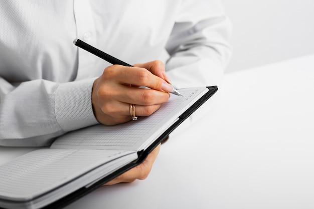 Geschäftsmann, der kenntnisse in ein notizbuch nimmt