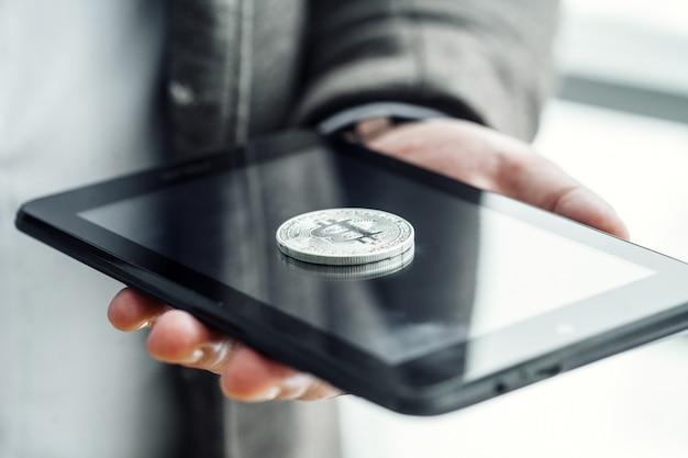 Geschäftsmann, der knopf bitcoin auf tablette bedrängt