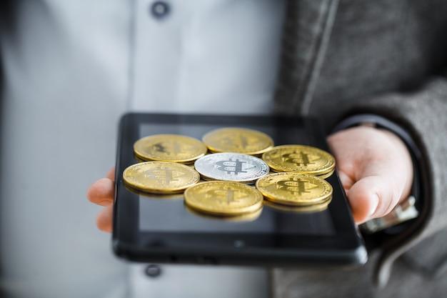 Geschäftsmann, der knopf bitcoin auf tablette drückt.