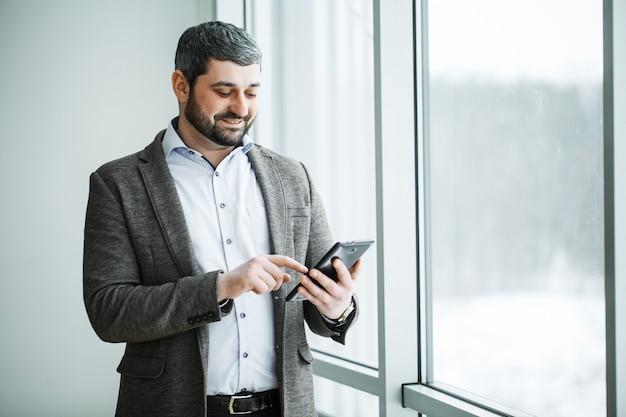 Geschäftsmann, der knopf bitcoin auf tablette drückt Premium Fotos