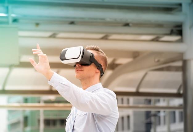 Geschäftsmann, der kopfhörer der virtuellen realität justiert. mann mit vr-headset zu arbeiten