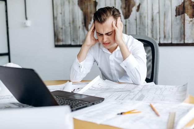 Geschäftsmann, der kopfschmerzen beim betrachten des laptops hat