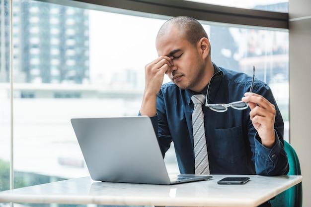 Geschäftsmann, der kopfschmerzen hat und an laptop im büro mit stadtgebäude arbeitet