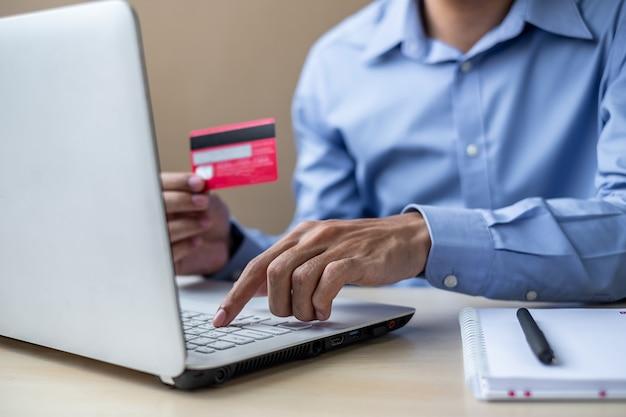 Geschäftsmann, der kreditkarte für das on-line-einkaufen hält