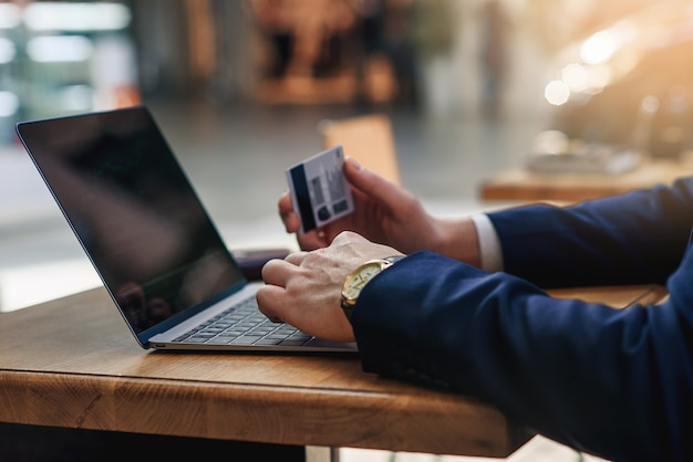 Geschäftsmann, der kreditkarte hält, die zahlen auf computertastatur tippt, während er am café am holztisch sitzt