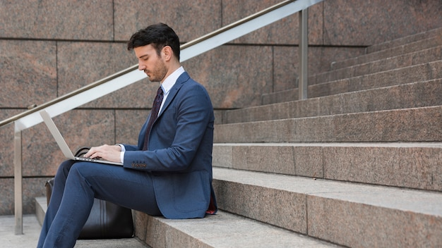 Geschäftsmann, der laptop auf schritten verwendet