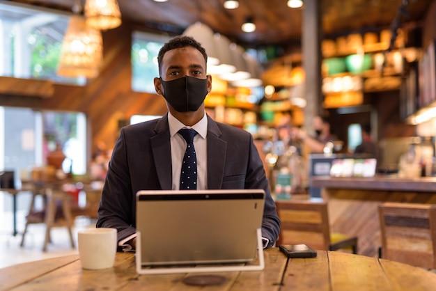 Geschäftsmann, der laptop beim tragen der gesichtsschutzmaske im kaffeehaus verwendet