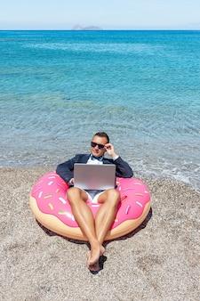 Geschäftsmann, der laptop-computer auf aufblasbarem donut am tropischen strand verwendet.