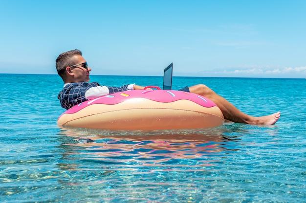 Geschäftsmann, der laptop-computer auf einem aufblasbaren donut im meer verwendet