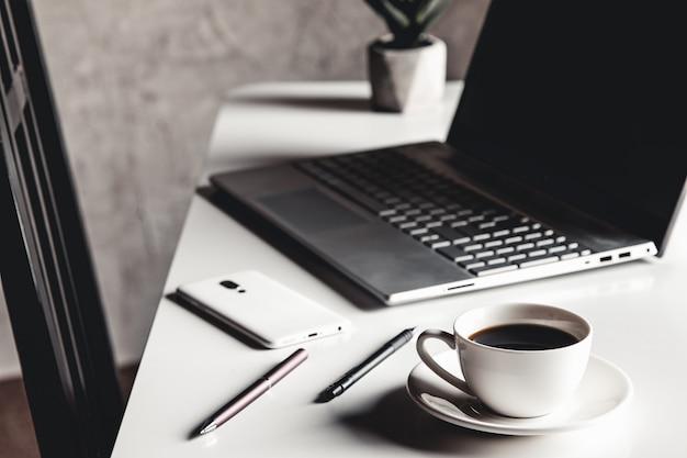 Geschäftsmann, der laptop-computer und hand, die auf laptop-tastatur mit notebook-stiftgläsern und tasse heißen kaffees tippt