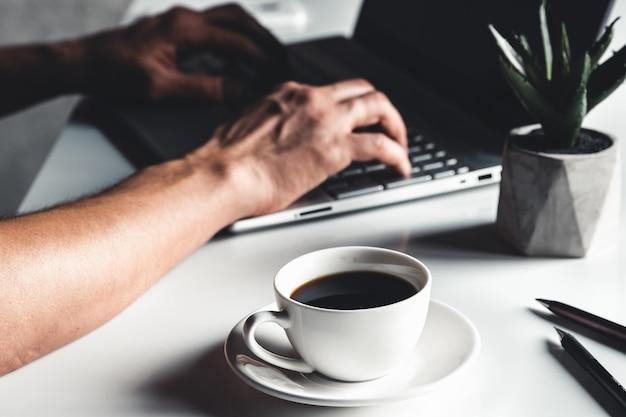 Geschäftsmann, der laptop-computer und hand-eingabe auf laptop verwendet