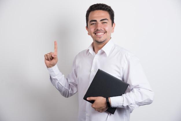 Geschäftsmann, der laptop hält und auf weißem hintergrund zeigt.