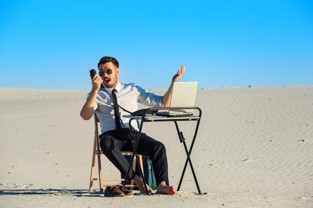 Geschäftsmann, der laptop in einer wüste benutzt
