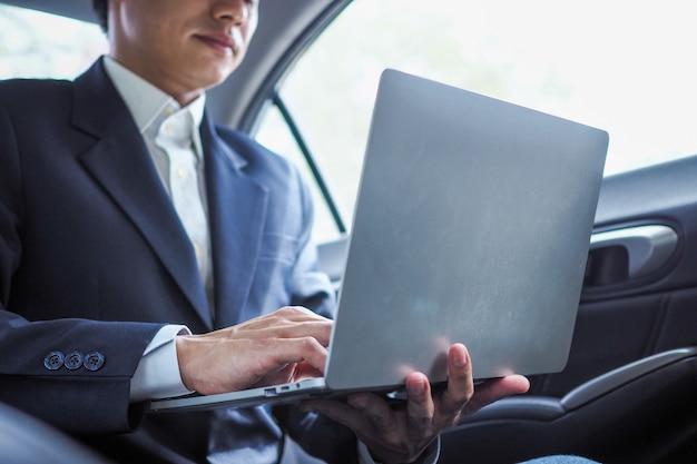 Geschäftsmann, der laptop verwendet, der am auto arbeitet