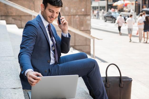 Geschäftsmann, der laptop verwendet und am telefon spricht
