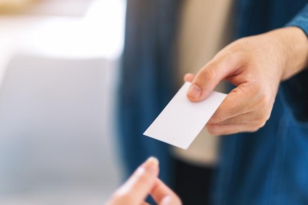Geschäftsmann, der leere visitenkarte hält und gibt