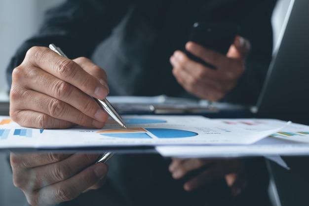 Geschäftsmann, der marktbericht analysiert, der im büro arbeitet