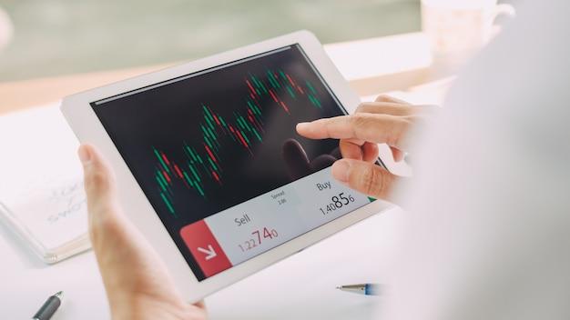 Geschäftsmann, der markthandel und austausch mit dokumentengraphiken auf intelligentem gerät analysiert.