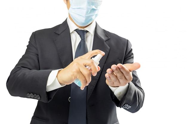 Geschäftsmann, der medizinische gesichtsmaske trägt, die hände desinfiziert