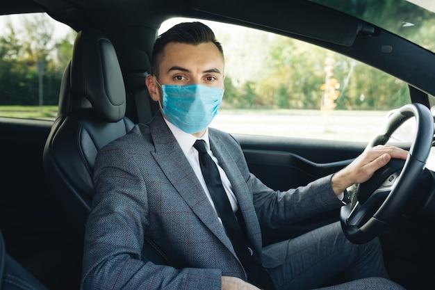Geschäftsmann, der medizinische maske zur vorbeugung gegen coronavirus trägt und sein auto zur arbeit fährt