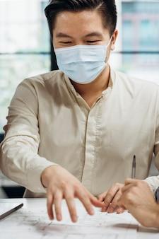 Geschäftsmann, der medizinische masken bei der arbeit trägt