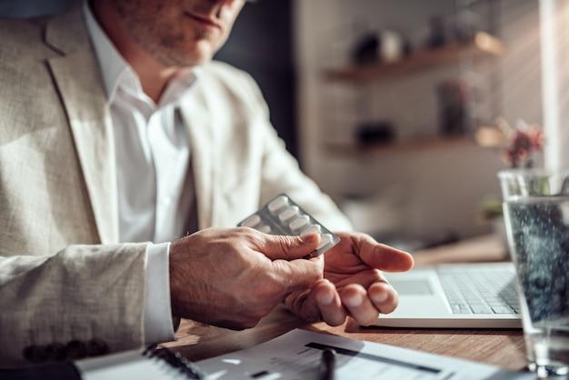 Geschäftsmann, der medizinische pillen im büro einnimmt