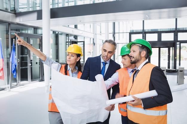Geschäftsmann, der mit architekten über blaupause diskutiert