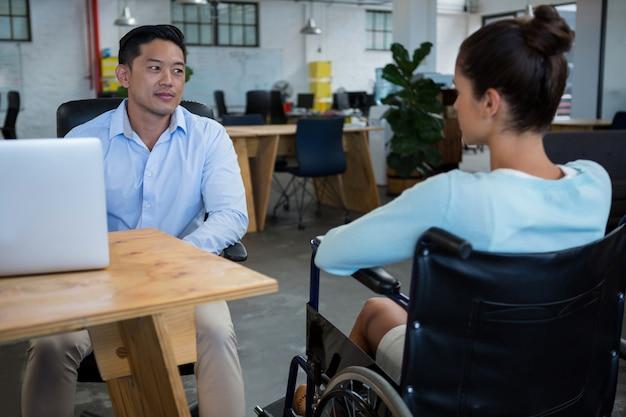 Geschäftsmann, der mit behindertem kollegen interagiert