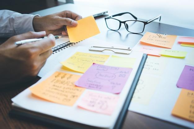Geschäftsmann, der mit briefpapier für brainstorming-ideen arbeitet
