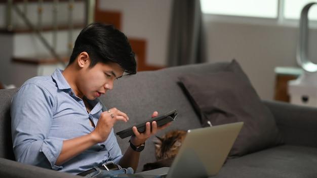 Geschäftsmann, der mit computer-laptop arbeitet und digitale tablette verwendet, während er zu hause auf dem sofa sitzt.