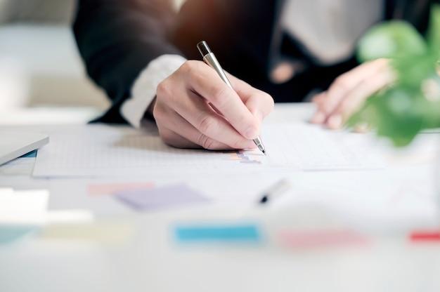 Geschäftsmann, der mit datendokumentdiagramm-diagrammbericht oder marktforschung, entwicklung im büro arbeitet.
