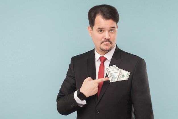 Geschäftsmann, der mit dem finger auf geld in der tasche eines bestechungsgeldes zeigt. indoor, studioaufnahme, isoliert auf hellblauem oder grauem hintergrund