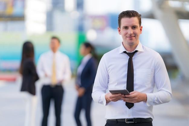 Geschäftsmann, der mit dem verwenden eines digitalen tabletts im stehen vor modernen bürogebäuden steht