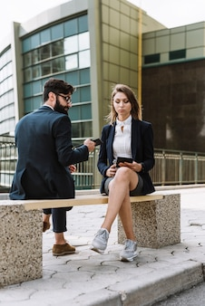 Geschäftsmann, der mit der geschäftsfrau betrachtet den smartphone sitzt auf bank sitzt