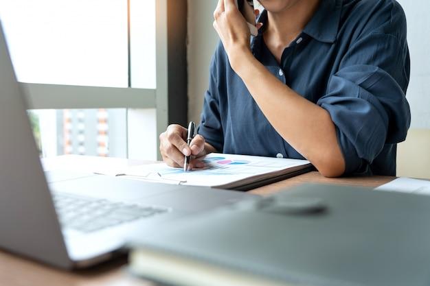 Geschäftsmann, der mit diagrammdaten im laptop und in den dokumenten arbeitet.