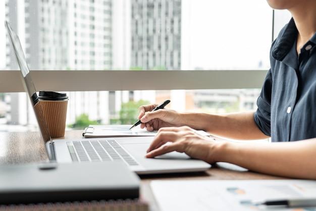 Geschäftsmann, der mit diagrammdaten im laptop und in den dokumenten auf seinem schreibtisch im büro arbeitet.