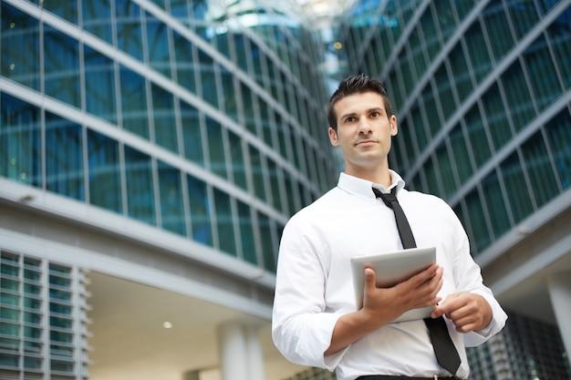 Geschäftsmann, der mit digitaler tablette in der städtischen umwelt arbeitet