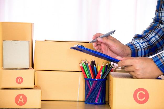 Geschäftsmann, der mit dokument arbeitet und braunen paketkasten verpackt.