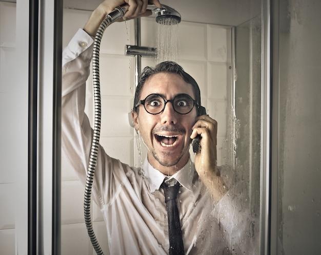 Geschäftsmann, der mit einem handy duscht