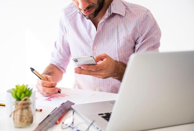 Geschäftsmann, der mit einem handy und einem laptop arbeitet