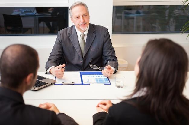 Geschäftsmann, der mit einem paar in seinem büro spricht
