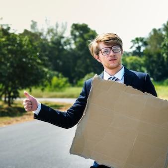 Geschäftsmann, der mit einem papierzeichen per anhalter fährt