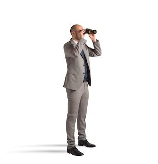Geschäftsmann, der mit fernglas auf weiß beobachtet