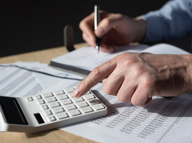 Geschäftsmann, der mit finanzdokumenten, buchhaltungsstatistiken arbeitet. steuerberechnungen und budgetkonzept.