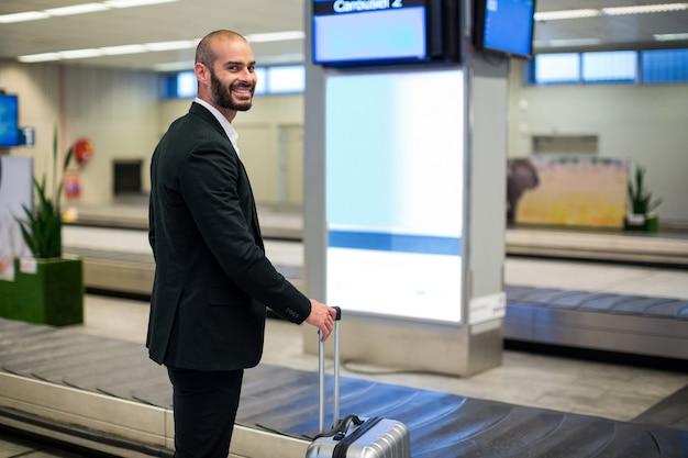 Geschäftsmann, der mit gepäcktasche im flughafen steht