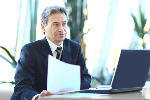 Geschäftsmann, der mit geschäftsdokumenten arbeitet, die an seinem schreibtisch sitzen. foto mit textfreiraum